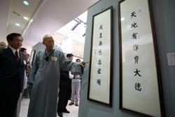 聖嚴師父親自為台南市長許添財(左)介紹展出作品。(陳志明 攝)